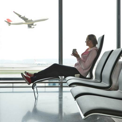 Airport transfers to from Swindon - lady looking at flight looking out of window at plane, drinking coffee